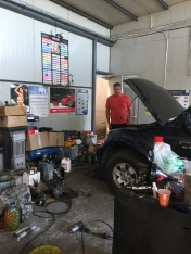 Luke at the mechanic. Look closely and you can see office decoration that would count as a sexual harassment lawsuit in Australia.