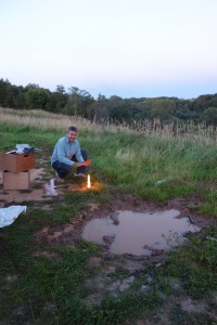 Classy scene. Luke warms his hands by our mud puddle.
