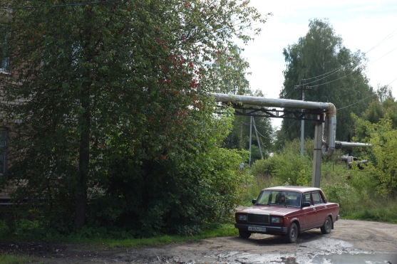 Old car framed by Soviet-style steam pipes, to heat the apartment blocks. Much Russia