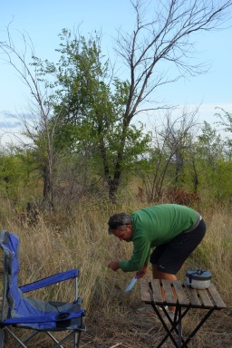 Luke cuts a dining room out of the grasses at our last free-camping spot in Russia.
