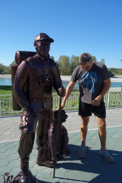 Luke pets a statue dog