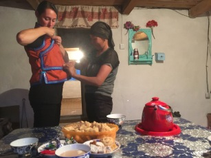 Joy's sister helps me try on a Mongolian vest, which her mother made
