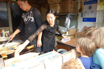 The kids watch as a vendor makes us delicious fried egg sandwiches