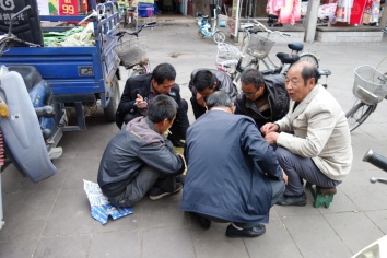 Men play mahjong on the street outside the city walls