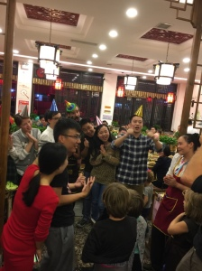 Jens and Bully (in red) help direct a crowd of strangers to sing happy birthday (in Chinese) in a video to Arne's Dad.