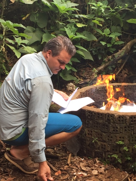 Luke burning paperwork we no longer need in Jhai's compost pile. No one needs old visa applications sitting around trash heaps in Southeast Asia.