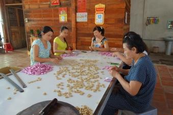 Ladies making and wrapping coconut candy by hand