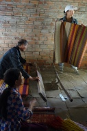 A craftscouple weaving dyed bamboo mats