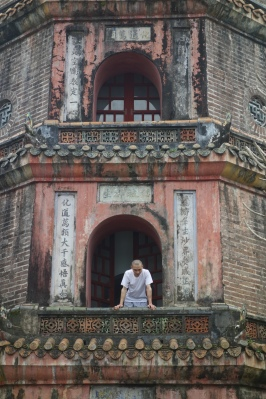 A monk takes a break from his work on the pagoda